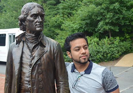 Anurag Chandran with a statue of Thomas Jefferson.