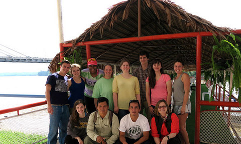 The Ecuador study abroad travelers pose under a palm thatch roof following a trip up the Napo River.